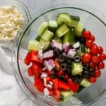 greek salad ingredients in a clear bowl with feta cheese on the side in a small clear bowl