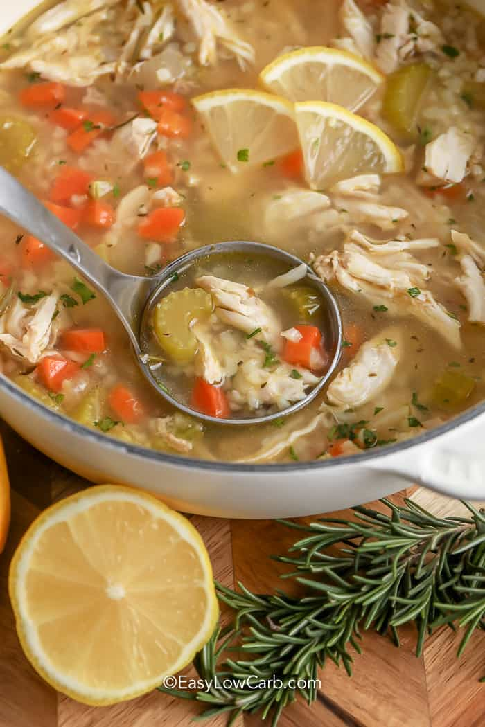 ladle dipping into a bowl of soup next to lemon and rosemary