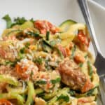 close up of feta zucchini pasta in a white bowl with text