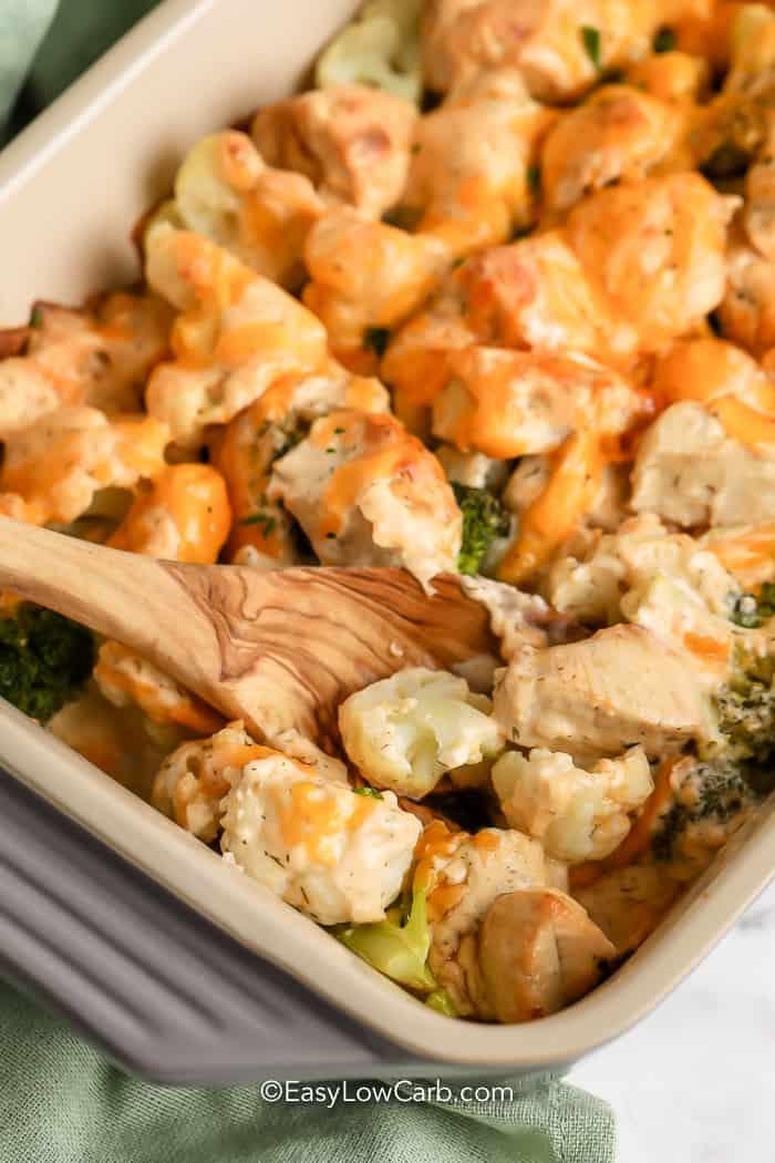 wooden spoon scooping Chicken Broccoli Cauliflower Casserole in a pan