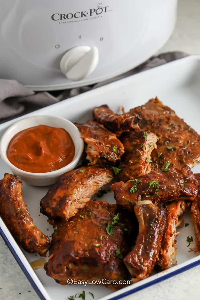 Crock Pot BBQ Ribs on a serving tray with sauce